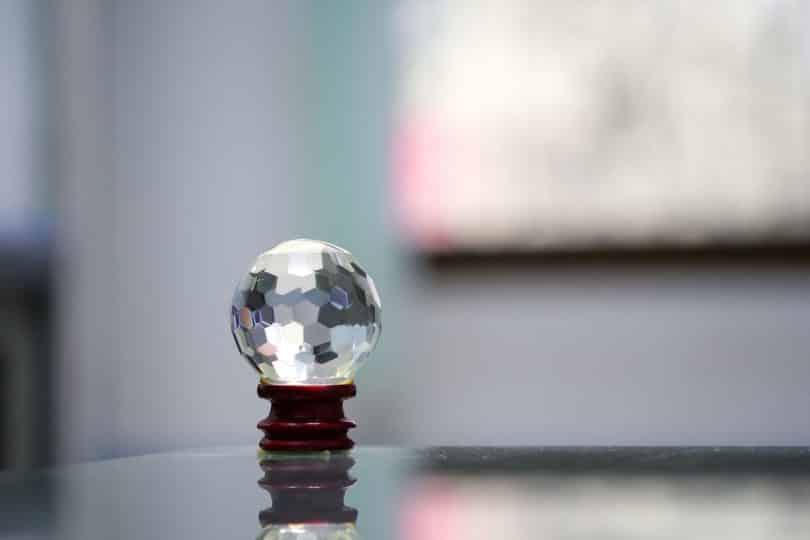 Cristal multifacetado: uma bola transparente em cima de um apoiador.