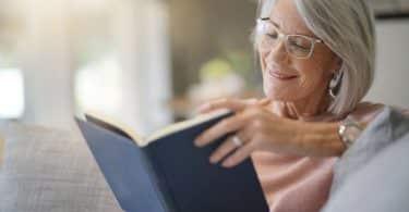 Mulher sentada no sofá lendo livro
