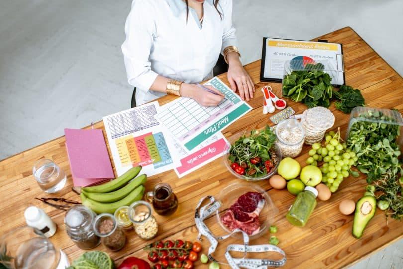Nutricionista em sua mesa com alimentos na mesa