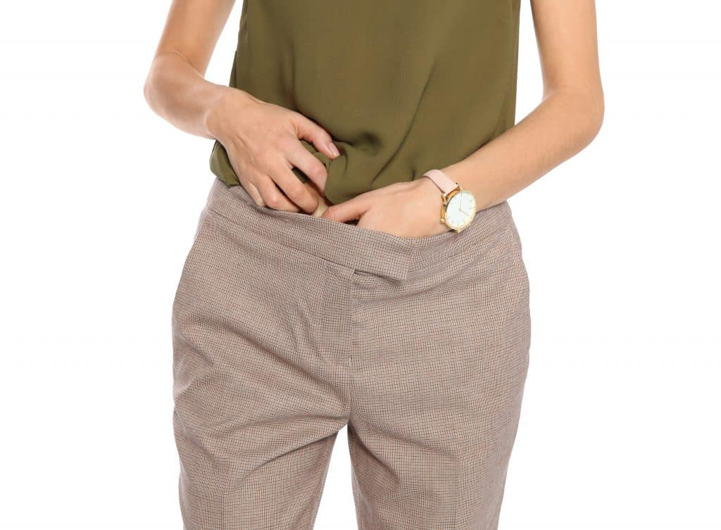 Imagem do corpo de uma mulher. Ela usa uma blusa verde e uma calça de linho bege. Ele está com sintomas da candidíase e está com as mãos dentro da calça.