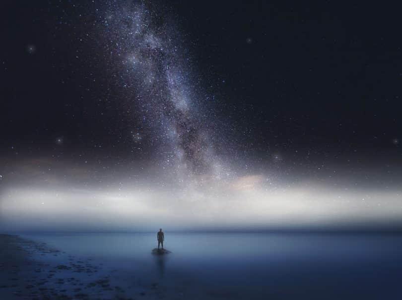 Silhueta de um homem em cima de uma pedra no meio do mar com um céu estrelado acima dele.