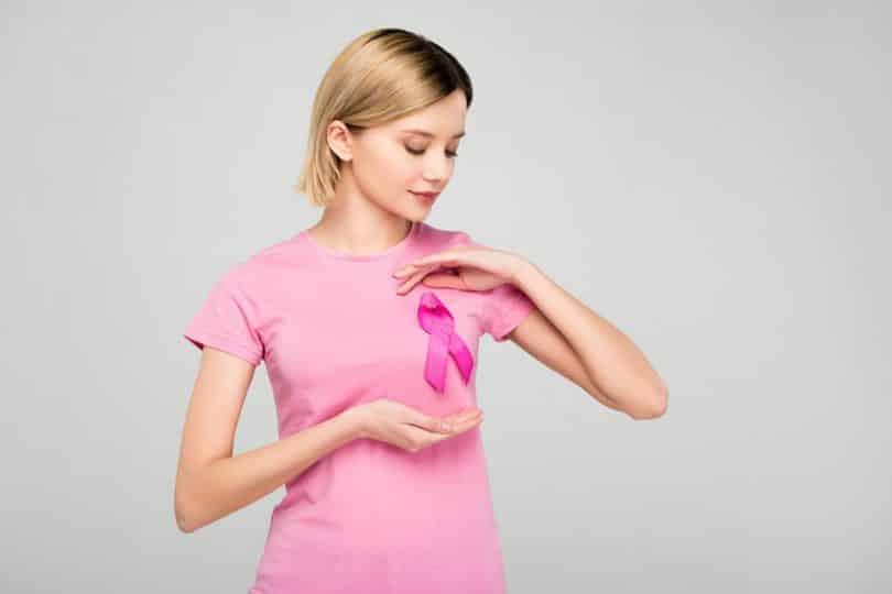 Mulher apontando para o laço sobre seu seio em homenagem ao Outubro Rosa