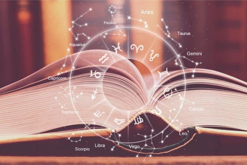 Livro aberto com desenho de horóscopo e signos brilhante em frente