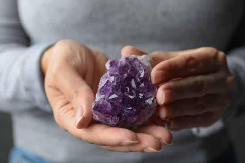 Mãos femininas segurando pedra ametista