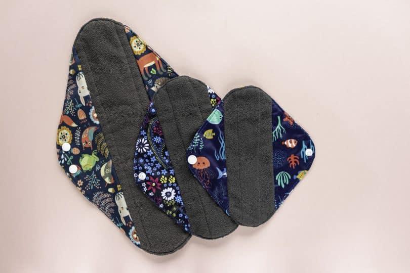 Imagem de três absorventes de pano nos tamanhos pequeno, médio e grande. Eles são feitos nas cores cinza e estampada.