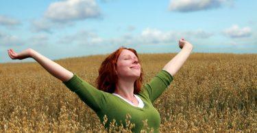 Mulher em campo com braços abertos e olhos fechados