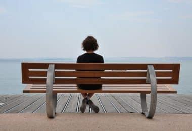 Pessoa sentada em um banco de madeira, em frente ao mar, em um dia nublado.