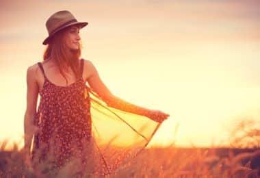 Mulher andando em campo com chapéu