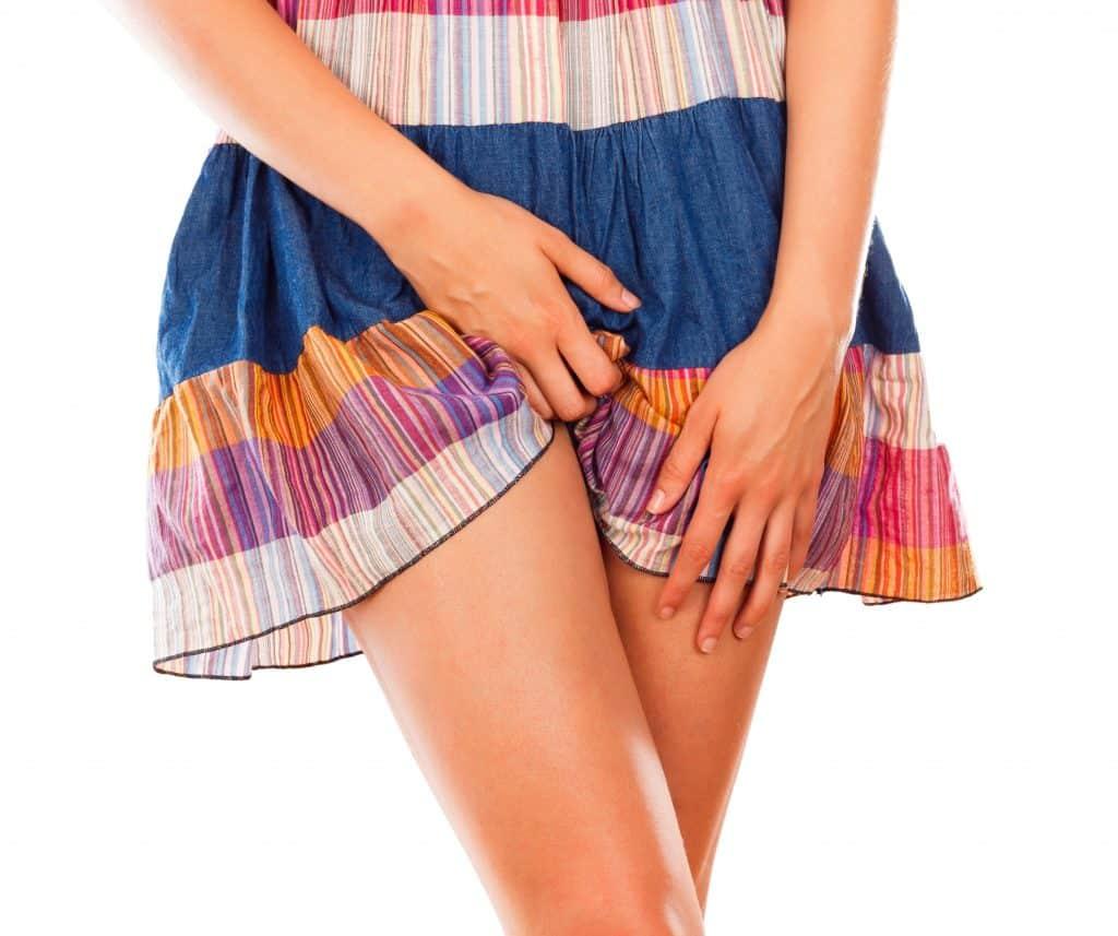 Imagem do corpo de uma mulher - da cintura para baixo. Ela usa uma saia colorida e está com uma das mãos sobre a sua genitália. Ela está com sintomas de candidíase.