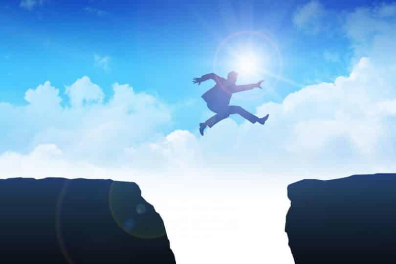Silhueta de um homem pulando por um buraco entre duas rochas