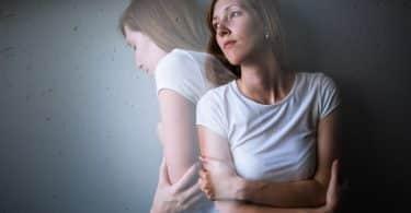 Mulher de camiseta branca com um semblante indiferente, à frente do seu próprio reflexo que demonstra tristeza.