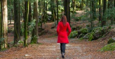 Mulher usando casaco vermelho caminhando numa floresta.