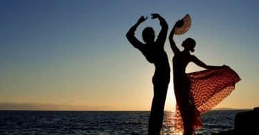 Silhueta de casal de dança com mar e pôr-do-sol ao fundo