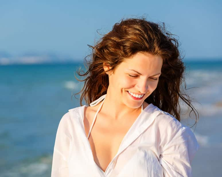 Mulher na praia sorrindo olhando para baixo com vento no cabelos