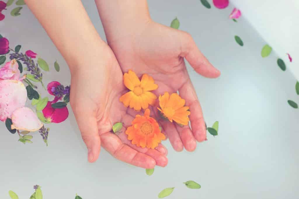 Mulher segurando flores na água da banheira