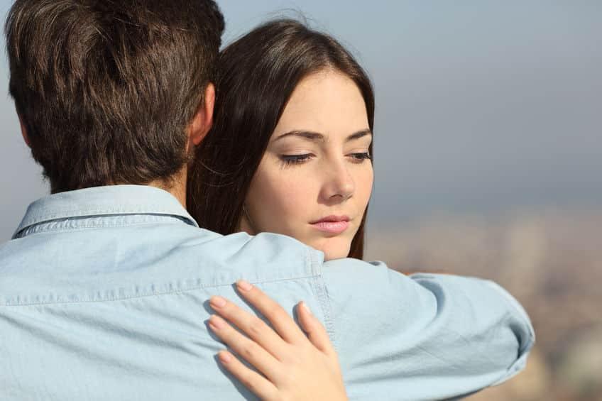 Mulher abraça homem enquanto olha para baixo, com expressão desconfiada.