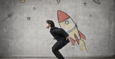 Homem com um um desenho de foguete nas costas em posição de quem vai decolar.