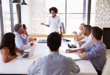 Mulher em pé em sala de reunião liderando