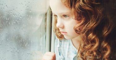 Garota na janela com expressão chateada