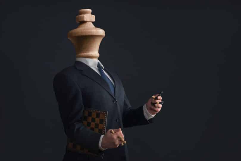 Corpo masculino com peça de xadrez no lugar da cabeça e segurando outros peças nas mãos.