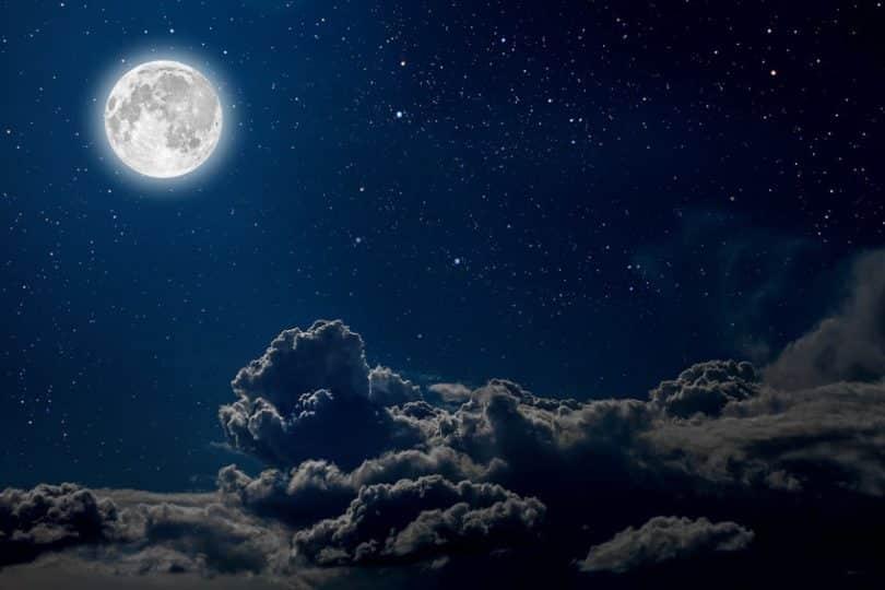 Céu noturno com uma lua cheia e nuvens.