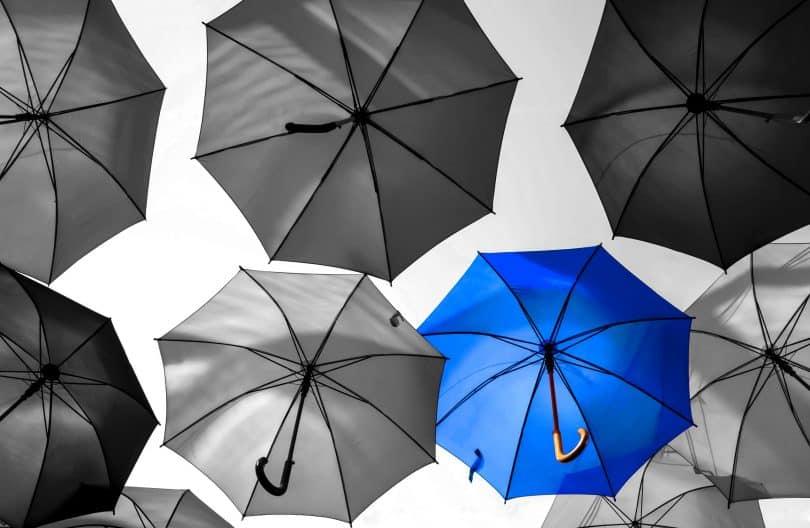 Guarda-chuva azul destacado em meio a outros cinzas.