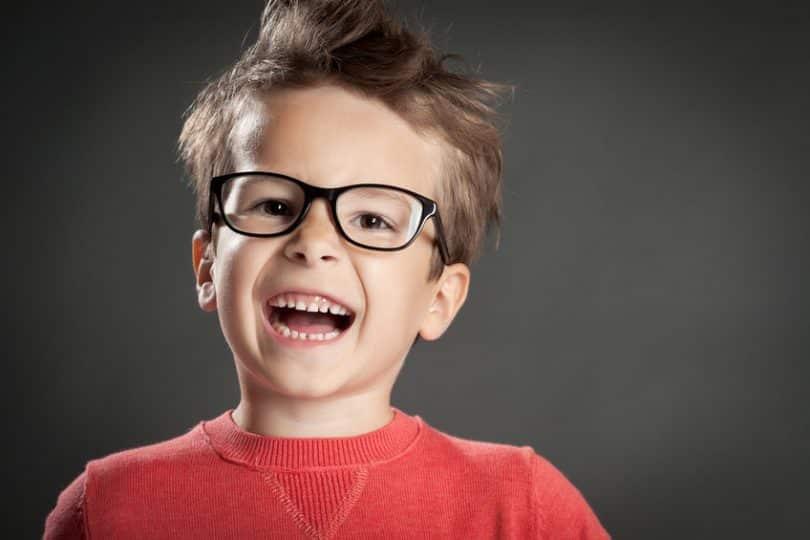 Garoto de suéter vermelho usando óculos sorrindo
