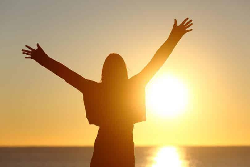 Mulher em frente a um por do sol. Ela está com os braços abertos.