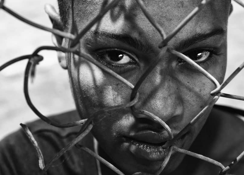 Close em rosto de mulher negra atrás de arame.