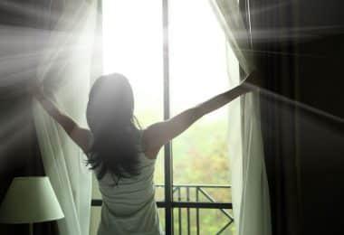Mulher abrindo a janela com luz refletindo
