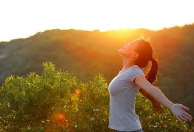 Mulher vista de perfil em um parque, com os braços abertos, sorrindo.
