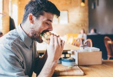 Homem em mesa de restaurante comendo lanche