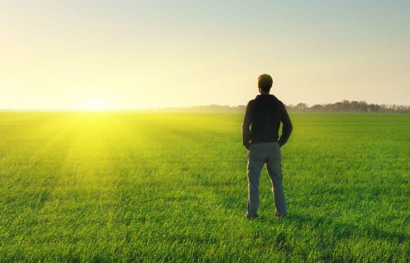 Homem em pé de costas em campo ver com sol se pondo ao fundo