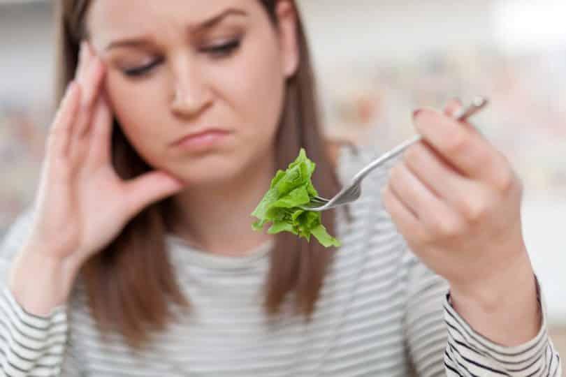 Mulher com expressão triste comendo salada