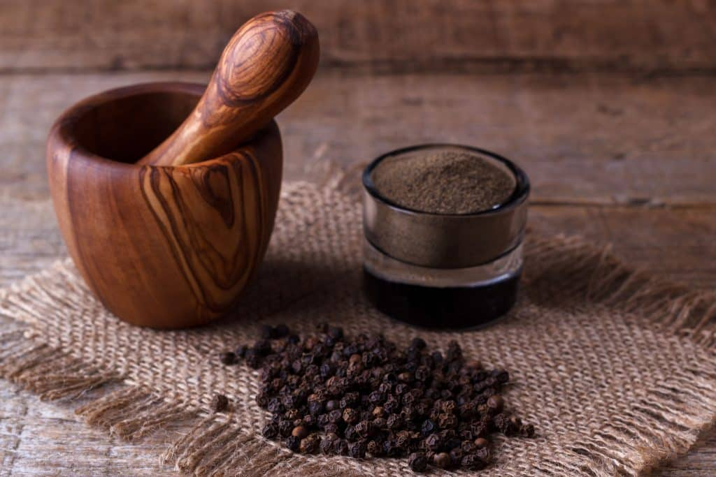 Pimenta preta triturada em um potinho e em frente a semente