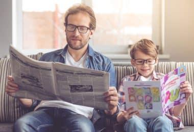 Homem e menino sentados em sofá com óculos lendo jornal e revista infantil