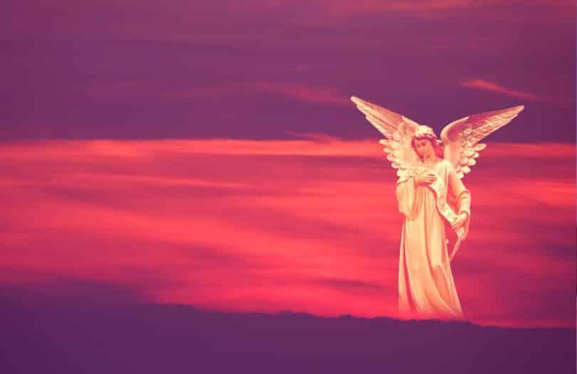Anjo visto no céu ao pôr do sol, entre as nuvens.
