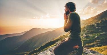 Homem ajoelhado no topo de uma montanha, com as mãos unidas em frente ao rosto, orando.