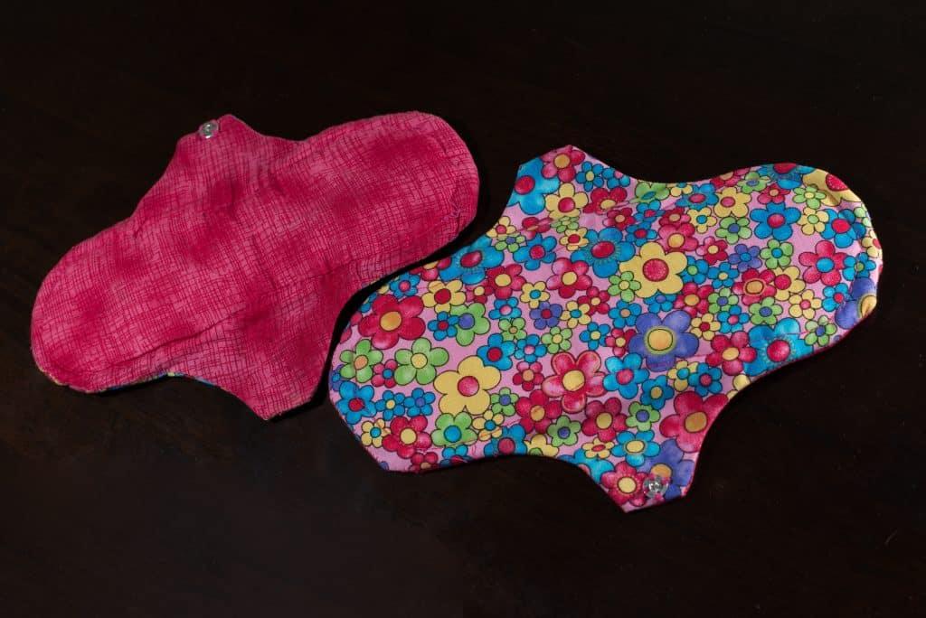 Imagem de um absorvente de pano nas cores rosa e estampada de florzinhas.