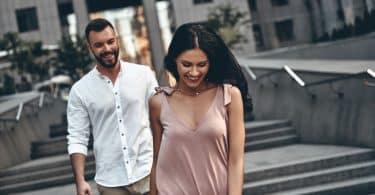 Homem e mulher caminhando juntos pela rua e rindo.