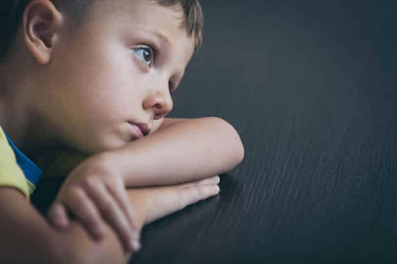 Garoto com rosto apoiado no braço e expressão triste