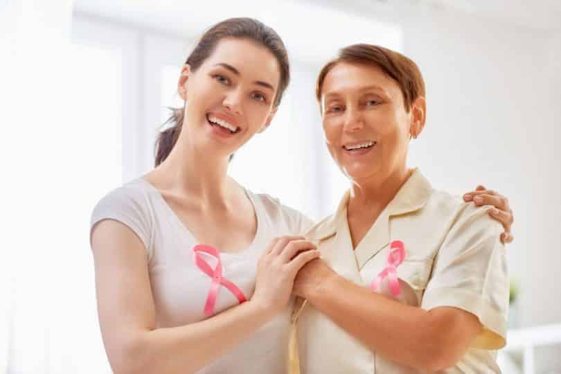 Mãe e filha abraçadas sorrindo com laço rosa no peito