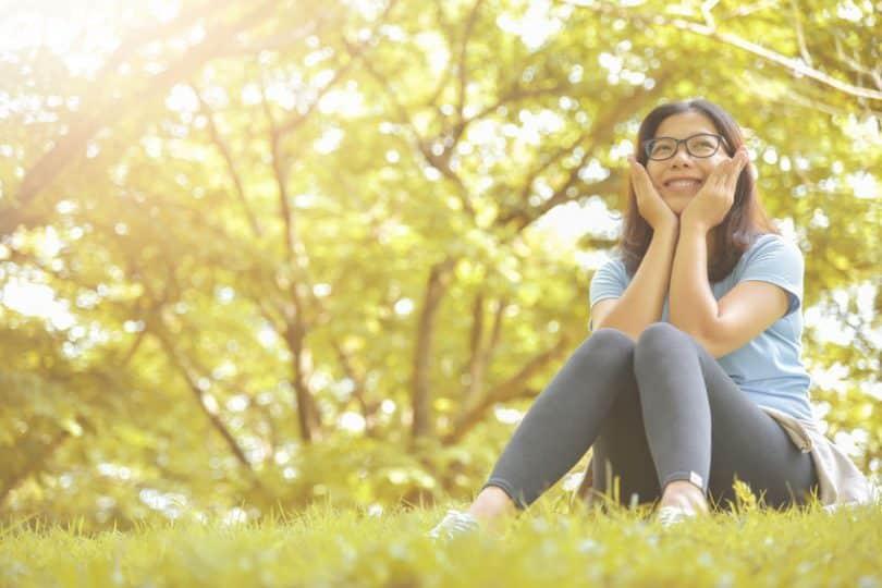 Mulher sentada em campo com maos no rosto sorrindo