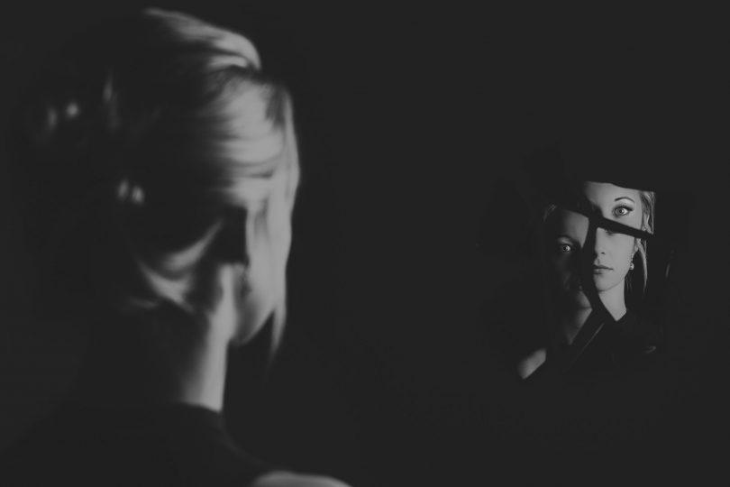 Mulher no escuro olhando o seu rosto em um espelho quebrado com pouca iluminação.
