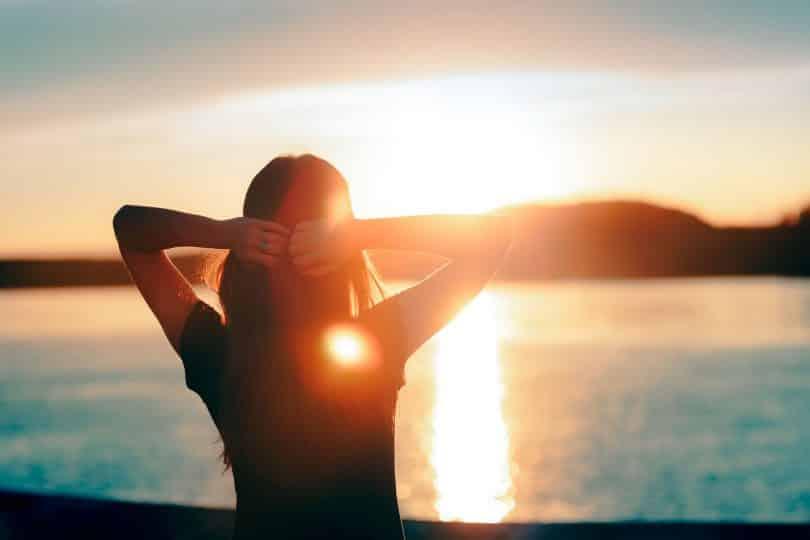 Mulher de costas com os braços abertos e mãos na nuca, de frente para um rio com pôr do sol.