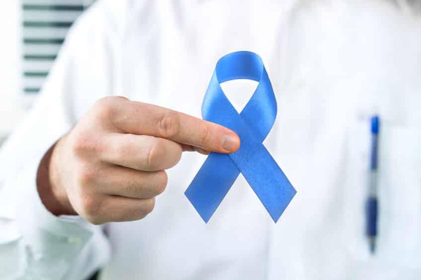 Médico segurando laço azul  em foco