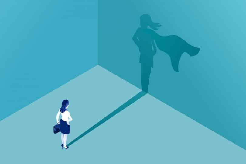 Ilustração de uma mulher olhando para a sua sombra na parede, que aparece com uma capa de super-heroína.