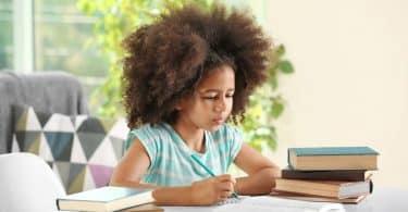 Menina na mesa de casa estudando com livros ao lado