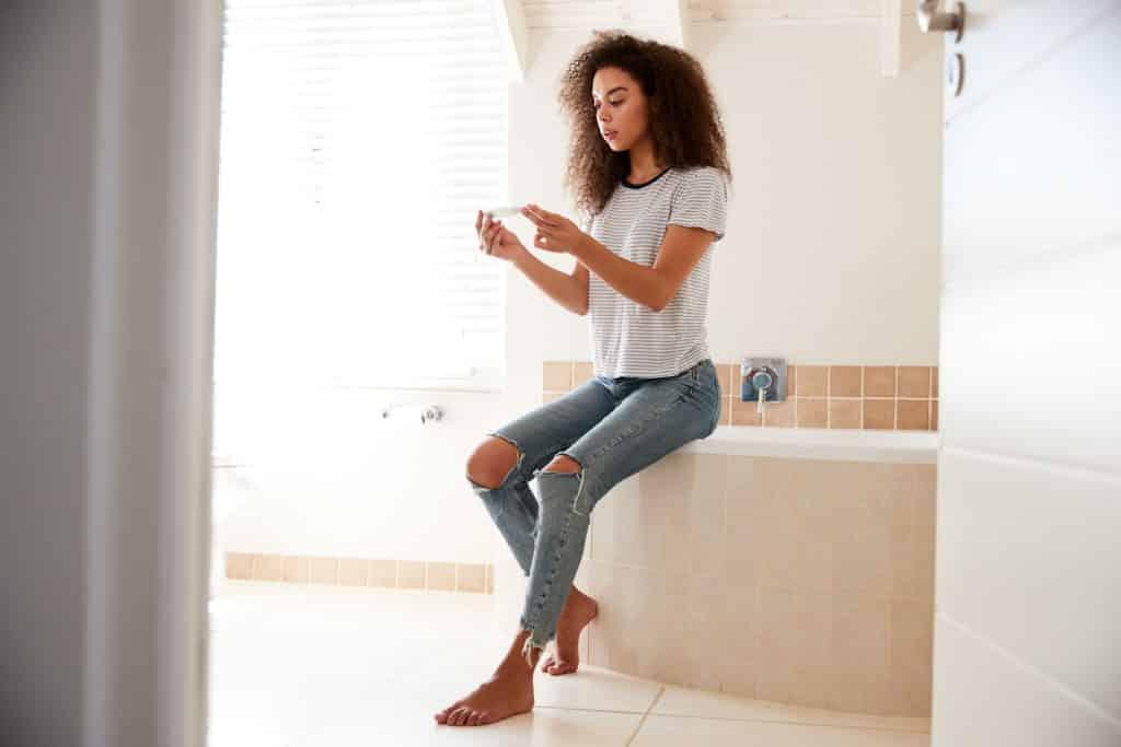 Mulher segurando teste de gravidez no banheiro