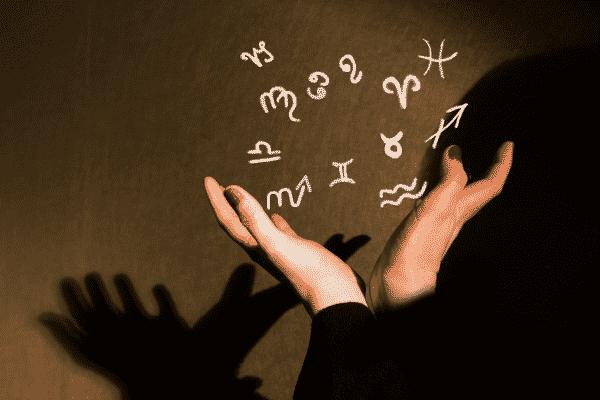 Mãos abertar com ícones de signos espalhados no ar